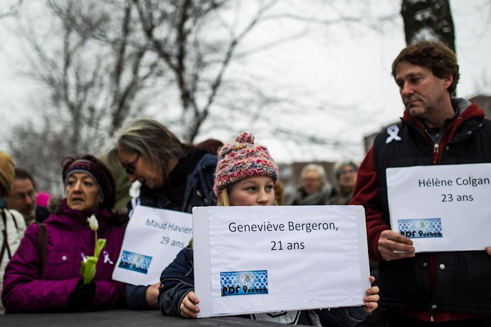 MONTREAL, CANADA - DECEMBER 6: Canadian pepople hold papers that bears the victim's names as people take part in a ceremony at the memorial park to mark the 25th anniversary of the Ecole Polytechnique massacre in Montreal, Canada on December 6, 2014. 25 years to the day, 25-year-old Marc Lepine killed 14 women at the École Polytechnique because of their gender. (Photo by Amru Salahuddien/Anadolu Agency/Getty Images)