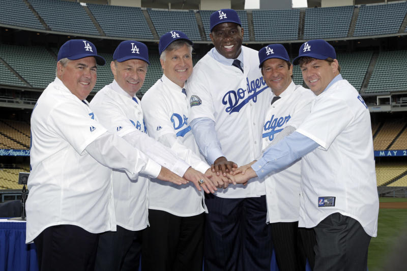 """New owners of the Los Angeles Dodgers, from left, Robert Patton, Stan Kasten, Mark Walter, Earvin """"Magic' Johnson,"""" Peter Guber, and Todd Boehly pose for a photo at Dodger Stadium in Los Angeles on Wednesday, May 2, 2012. The $2 billion sale of the team to Guggenheim Baseball Management was finalized Tuesday. (AP Photo/Damian Dovarganes)"""