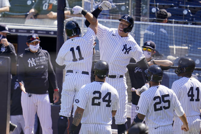 New York Yankees' Brett Gardner (11) celebrates his grand slam off Philadelphia Phillies starting pitcher Zack Wheeler, with Aaron Judge, top right center, and manager Aaron Boone, left, during the second inning of a spring training exhibition baseball game against the Philadelphia Phillies at George M. Steinbrenner Field in Tampa, Fla., Sunday, March 7, 2021. (AP Photo/Gene J. Puskar