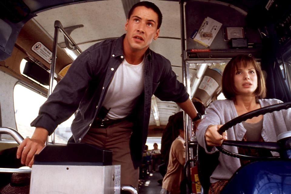 Reeves stands over Bullock as she drives the bus at high speed