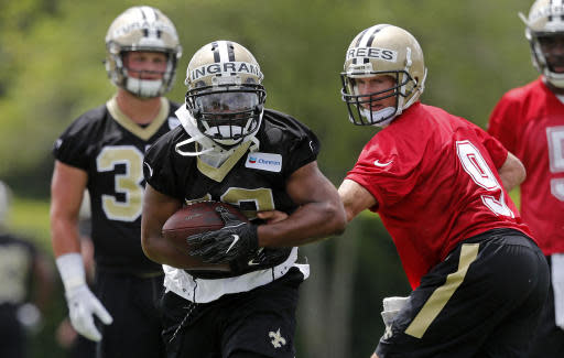 New Orleans Saints quarterback Drew Brees (9) hands off to running back Mark Ingram (22) during NFL football practice in Metairie, La., Tuesday, June 12, 2018. (AP Photo/Gerald Herbert)