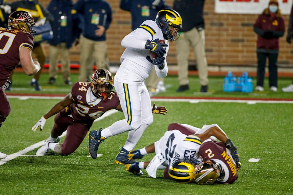 Michigan defensive lineman Donovan Jeter catches the ball en route to a touchdown past running back Mohamed Ibrahim after linebacker Michael Barrett knocked it loose from Minnesota quarterback Tanner Morgan in the first quarter on Saturday, Oct. 24, 2020, in Minneapolis.