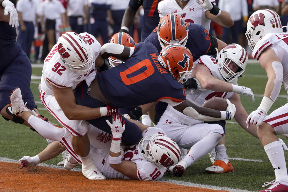 Illinois running back Joshua McCray sticks the ball over the goal line to avoid a safety as Wisconsin defensive end Matt Henningsen (92) and Collin Wilder (18) make the tackle during the first half of an NCAA college football game Saturday, Oct. 9, 2021, in Champaign, Ill. (AP Photo/Charles Rex Arbogast)