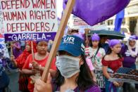 A women's rights activist wears a protective mask amid the coronavirus scare during a rally on International Women's Day in Manila