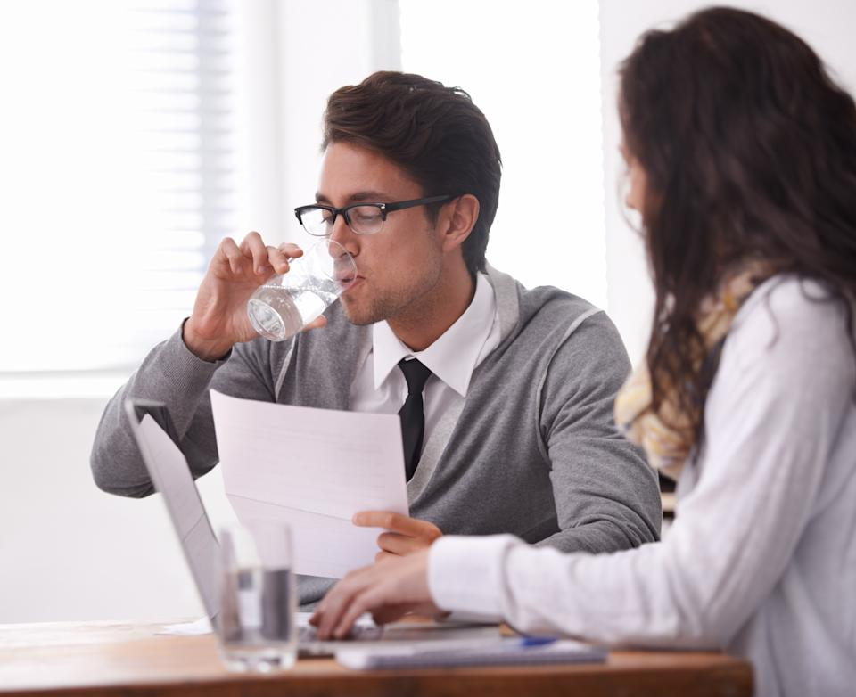 Pictured: Job interview with man drinking glass of water. Image: Getty