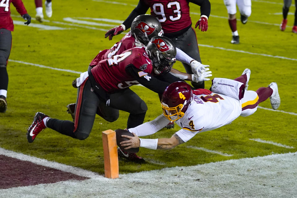 Washington football quarterback Taylor Heinicke (4) dived to mark a touchdown against Tampa Bay Buccaneers with defenders Kevin Minter (51) and Lavonte David (54) during the second half of an NFL playoff game. wild card, Saturday, January 9, 2021, in Landover, Md.  (AP Photo / Julio Cortez)