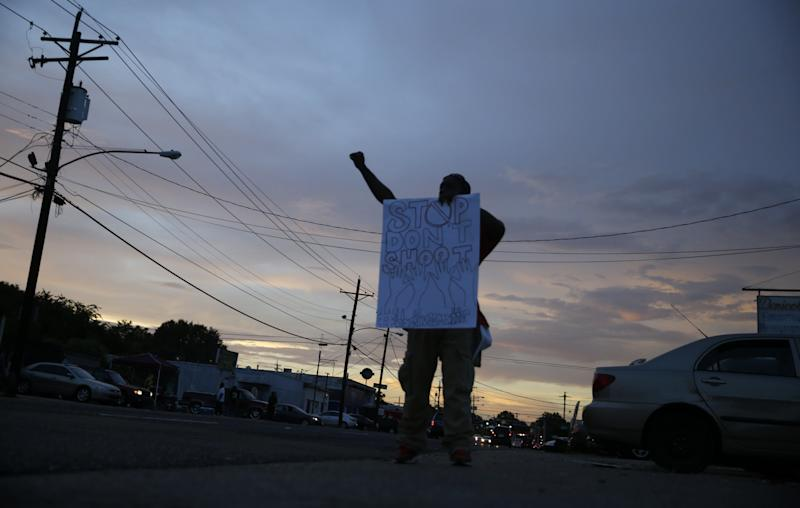 Troy Holliday, of Baton Rouge, holds a sign and gestures to passing motorists in honor of Alton Sterling, outside the Triple S Food Mart in Baton Rouge, La., Monday, July 11, 2016. Sterling was shot and killed last Tuesday by Baton Rouge police while selling CD's outside the convenience store. (AP Photo/Gerald Herbert)