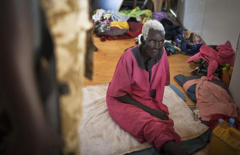 An elderly woman who hid from rebels in an office during the recent fighting, speaks to a South Sudanese government soldier, left, in Bor, Jonglei State, South Sudan Sunday, Jan. 19, 2014. Leaders for warring sides in South Sudan's monthlong internal conflict say they are close to signing a cease-fire and the South Sudanese military spokesman said that army forces had retaken the key city of Bor Saturday, defeating 15,000 rebels. (AP Photo/Mackenzie Knowles-Coursin)