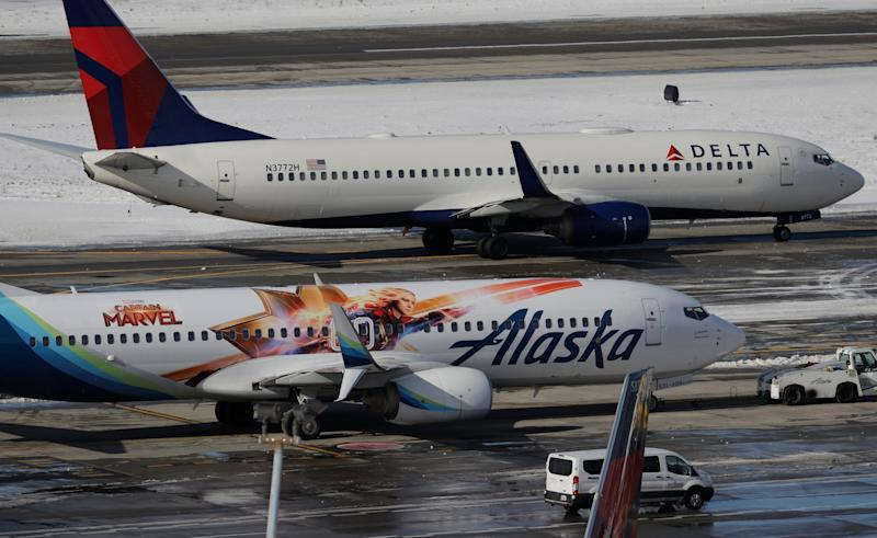 A Delta Air Lines plane taxis past an Alaska Airlines plane with their Captain Marvel livery, Tuesday, Feb. 5, 2019, near a snow-bordered runway at Seattle-Tacoma International Airport in Seattle. (AP Photo/Ted S. Warren)