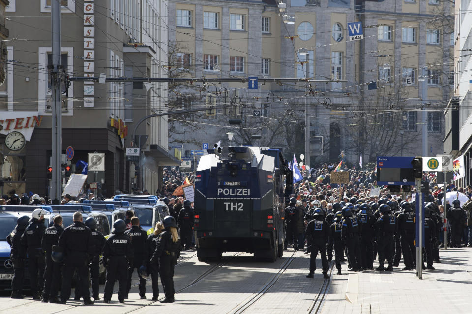 "Police forces stand next to a water canon during a rally under the motto ""Free citizens Kassel - basic rights and democracy"" i Kassel, Germany, Saturday, March 20, 2021. According to police, several thousand people were on the move in the city center and disregarded the instructions of the authorities during the unregistered demonstration against Corona measures. (Swen Pfoertner/dpa via AP)"