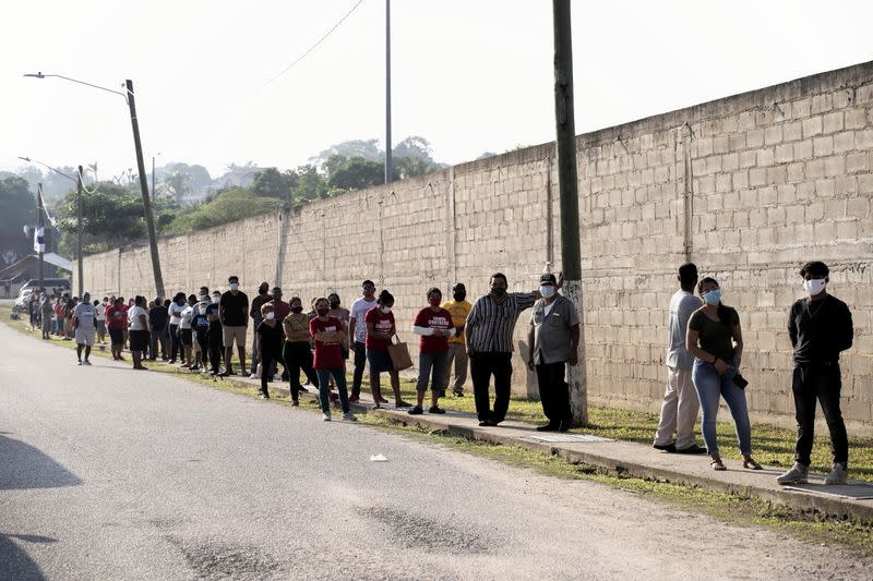 People queue outside a polling station to cast their vote during the election for a new prime minister, in Benque Viejo del Carmen