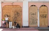 Tourists wait in front of boarded-up storefronts as they prepare to leave Miami Beach ahead of Hurricane Irma