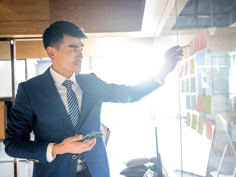 chinese manager sticking post-it notes