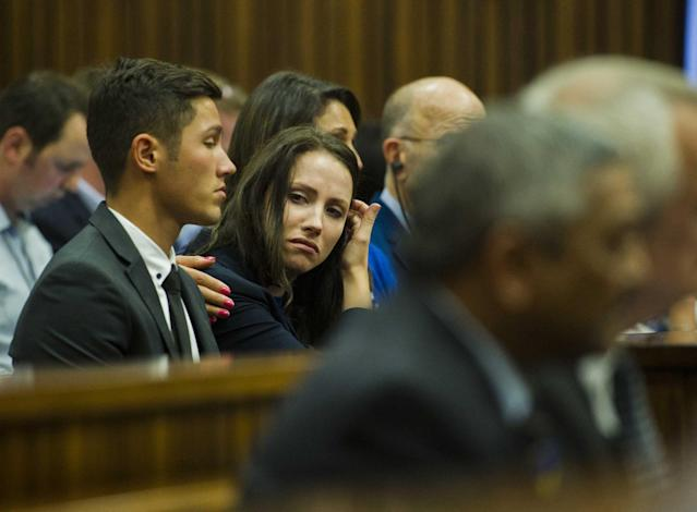 Sister of Oscar Pistorius, Aimee Pistorius, center, is comforted as she listens to forensic evidence during his trial in court in Pretoria, South Africa, Thursday March 13, 2014. Pistorius is charged with the shooting death of his girlfriend Reeva Steenkamp, on Valentines Day in 2013. (AP Photo/Alet Pretorius, Pool)