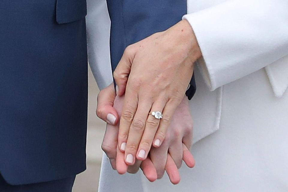 """<p>The prince selected two diamonds from his mother's collection to flank a <a href=""""https://www.goodhousekeeping.com/beauty/fashion/news/a47857/meghan-markle-first-engagement-ring/"""" rel=""""nofollow noopener"""" target=""""_blank"""" data-ylk=""""slk:central cushion-cut stone"""" class=""""link rapid-noclick-resp"""">central cushion-cut stone</a> sourced from Botswana. For the band, he chose yellow gold—<span class=""""redactor-unlink"""">Meghan's favorite</span>.</p>"""