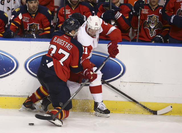 Florida Panthers' Nick Bjudstad (27) and Detroit Red Wings' Daniel Alfredsson (11) battle for the puck during the second period of a NHL hockey game in Sunrise, Fla., Tuesday, Dec. 10, 2013. (AP Photo/J Pat Carter)