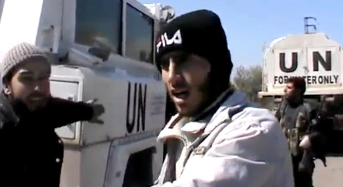 In this Wednesday, March 6, 2013 image taken from video obtained from the Ugarit News, which has been authenticated based on its contents and other AP reporting, Free Syrian Army fighters stand next to United Nations Disengagement Observer vehicles near Golan Heights in the southern province of Daraa, Syria. Clashes between Syrian troops and rebel fighters flared on Thursday near an area where armed fighters linked to the opposition abducted 21 U.N. peacekeepers a day earlier. In an online video, a man identified as a spokesman for the Martyrs of Yarmouk Brigades said his group will hold the peacekeepers until Assad's forces withdraw from Jamlah. (AP Photo/Ugarit News via AP video)
