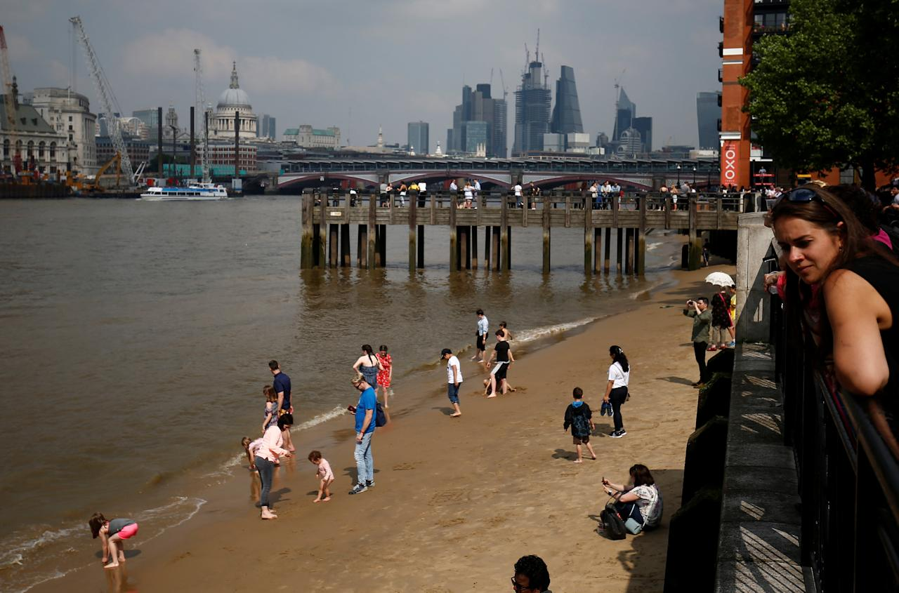 Tourists walk on a beach exposed from beneath the River Thames by a low tide, next to the South Bank in central London, Britain May 27, 2018.  REUTERS/ Henry Nicholls