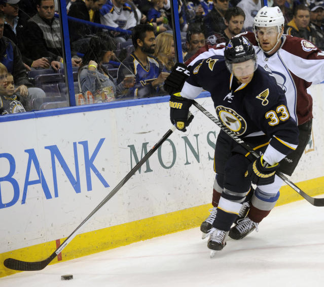 St. Louis Blues' Jordan Leopold (33) skates around Colorado Avalanche's Brad Malone during the first period of an NHL hockey game, Saturday, April 5, 2014, in St. Louis. (AP Photo/Bill Boyce)