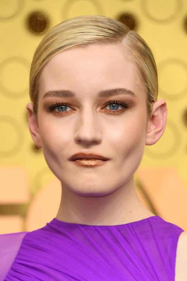 Ozark actress Julia Garner paired bronze metallic eyeshadow with a bronze lip. For her hair, celebrity hairstylist Bobby Eliot slicked Julia's blonde locks back into a side-parted, low-bun.