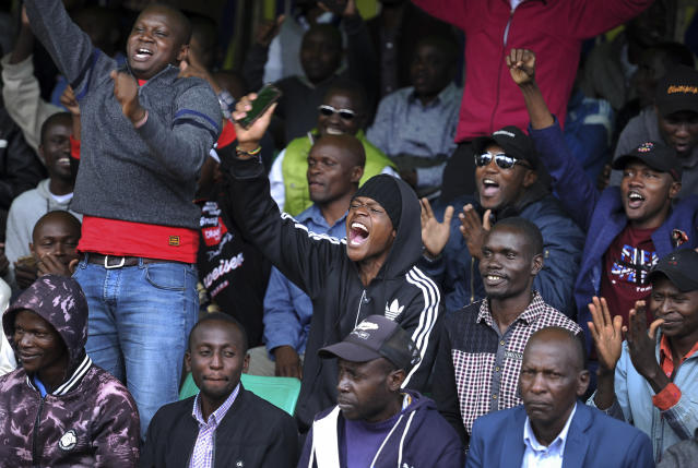 Kenyans celebrate Eliud Kipchoge's sub-2 hour marathon time, outside the Kenya International Conference Center in downtown Nairobi, Kenya Saturday, Oct. 12, 2019. Eliud Kipchoge has become the first athlete to run a marathon in less than two hours, at an event set up for the attempt in Austria, although it will not count as a world record. (AP Photo/John Muchucha)