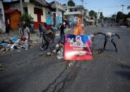 Demonstrators set up a burning barricade using a campaign poster for a referendum on a change of the constitution, during a protest against the government of President Jovenel Moise, in Port-au-Prince