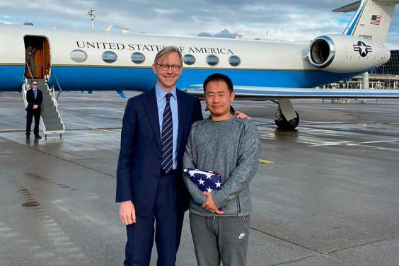Xiyue Wang, right, with Brian Hook, the US representative for Iran, at an airport in Zurich, Switzerland, following his release from jail in Iran as part of a prisoner swap (AP)