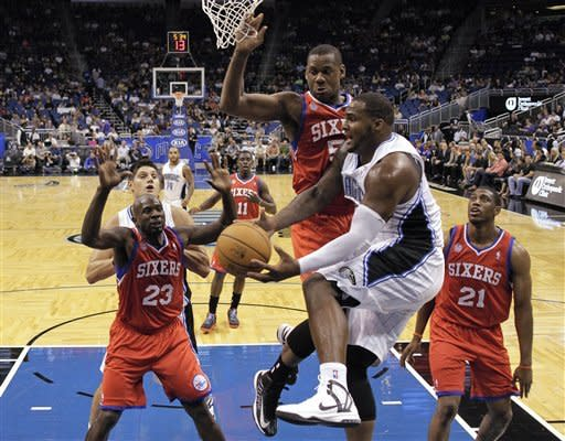 Orlando Magic's Glen Davis, center, passes the ball out from under the basket as he is guarded by Philadelphia 76ers' Jason Richardson (23), Lavoy Allen, and Thaddeus Young (21) during the first half of an NBA preseason basketball game, Thursday, Oct. 11, 2012, in Orlando, Fla. (AP Photo/John Raoux)