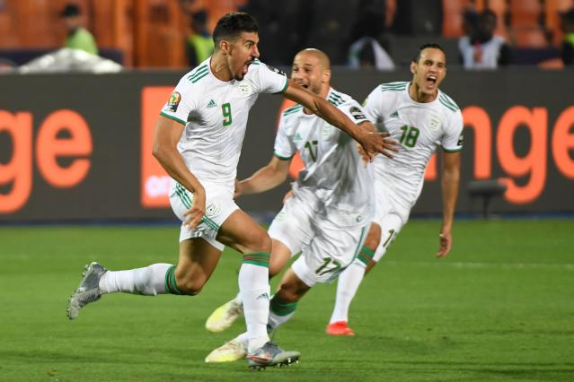 Algeria's Baghdad Bounedjah (9) celebrates with teammates after scoring the first and only goal of the 2019 Africa Cup of Nations final against Senegal. (Getty)