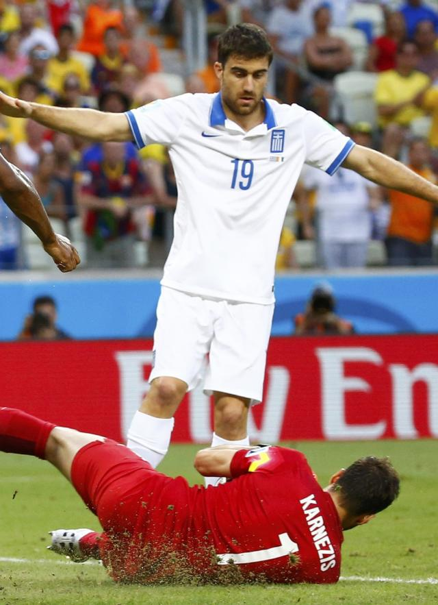 Greece's Karnezis falls and injures himself in front of teammate Papastathopoulos during their 2014 World Cup Group C soccer match against Ivory Coast at the Castelao arena in Fortaleza