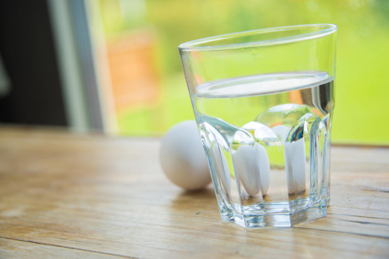 two eggs and a glass of water on a wooden table