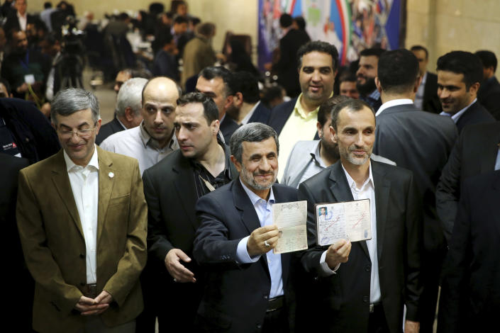 Former Iranian President Mahmoud Ahmadinejad, center, and his close ally Hamid Baghaei, right, show their identifications after registering their candidacy for the upcoming presidential elections at the Interior Ministry to , in Tehran, Iran, Wednesday, April 12, 2017. Ahmadinejad on Wednesday unexpectedly filed to run in the country's May presidential election, contradicting a recommendation from the supreme leader to stay out of the race. Other close ally of Ahmadinejad, Esfandiar Rahim Mashie accompanies them. (AP Photo/Ebrahim Noroozi)