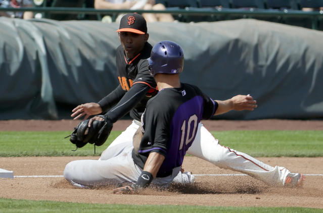 Colorado Rockies Paul Janish, right, is tagged out by San Francisco Giants third baseman Joaquin Arias while trying to advance on a ball hit by Jorge De La Rosa during the second inning of an exhibition baseball game in Scottsdale, Ariz., Wednesday, March 26, 2014. (AP Photo/Chris Carlson)