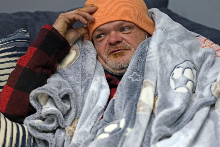 Brett Saint rests inside a Gallery Furniture store which opened as a shelter for those in need of food, water and heat Wednesday, Feb. 17, 2021, in Houston. Millions in Texas still had no power after a historic snowfall and single-digit temperatures created a surge of demand for electricity to warm up homes unaccustomed to such extreme lows, buckling the state's power grid and causing widespread blackouts. (AP Photo/David J. Phillip)