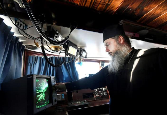 Father Abbot Abibos turns on the radar in the wheelhouse of a mobile Georgian Orthodox monastery in Vlissingen