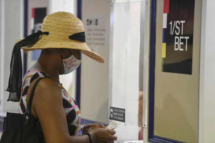 A woman wears a face mask to protect against the spread of COVID-19 and a hat while placing a bet ahead of the Preakness Stakes horse race at Pimlico Race Course, Saturday, May 15, 2021, in Baltimore. (AP Photo/Will Newton)
