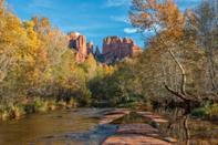"""Arizona might not scream fall sights but Oak Creek Canyon—a stunning red rock canyon just north of <a href=""""https://www.cntraveler.com/hotels/united-states/happy-jack/l-auberge-de-sedona-sedona?mbid=synd_yahoo_rss"""" rel=""""nofollow noopener"""" target=""""_blank"""" data-ylk=""""slk:Sedona"""" class=""""link rapid-noclick-resp"""">Sedona</a>—provides its own kind of colorful rewards for hikers, changing trees included. Mostly shaded (a plus in the southwest heat), the six-ish mile West Fork Trail will bring you through a side canyon with multiple creek crossings (bring shoes you don't mind getting a little wet). Just note: You likely won't be the only one seeking refuge in the forest and creeks, as West Fork is often touted as one of the best trails in Coconino National Forest."""