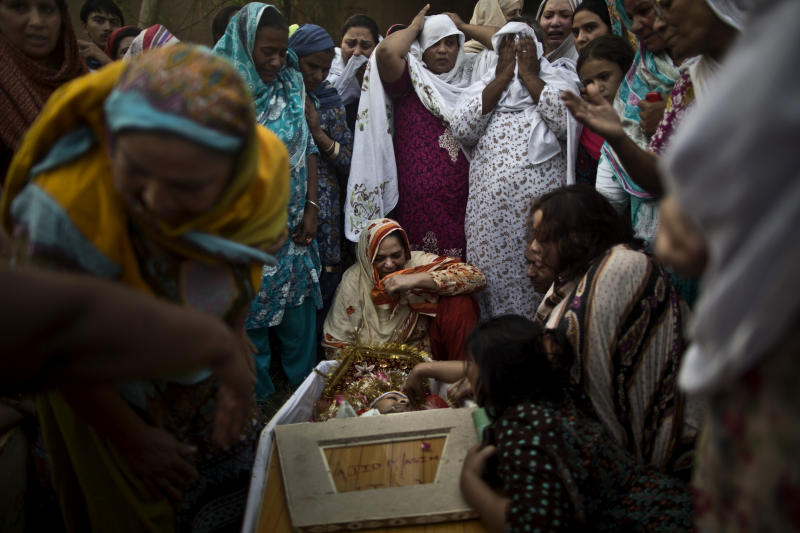 In this Sunday, Sept. 22, 2013, photo, Pakistani women grieve over coffins of their relatives who were killed in a suicide attack on a church in Peshawar, Pakistan. A Sunni militant group known for targeting rival Muslims has emerged as a dangerous new player in Pakistan, sending a pair of suicide bombers to stage the deadliest ever attack against Pakistani Christians. The brutal assault, killed tens of worshippers on Sunday, Sept. 22, 2013. (AP Photo/Muhammed Muheisen)