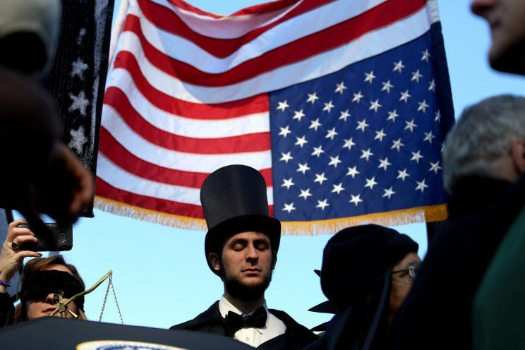 A man dressed as Abraham Lincoln listens during a mock funeral for the American presidency in New York City on Saturday. (Bria Webb/Reuters)