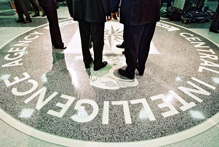 people standing on CIA logo in CIA headquarters