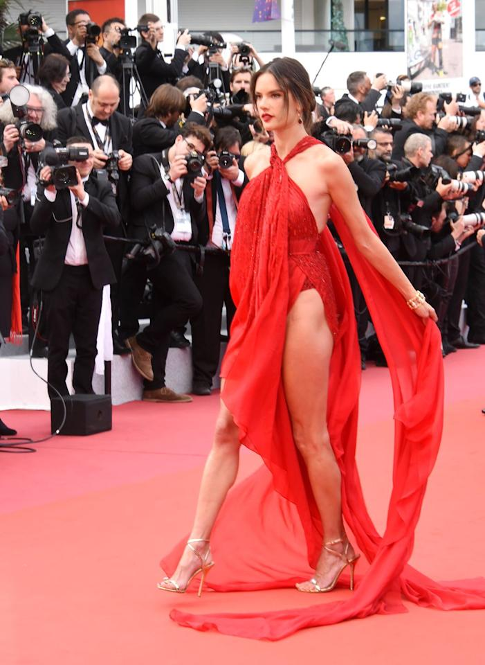 <p>The model made an appearance at Cannes in a stunning red halter dress that had a super high side slit. The Julien Macdonald number flowed in the wind as the model worked it for the cameras.</p>