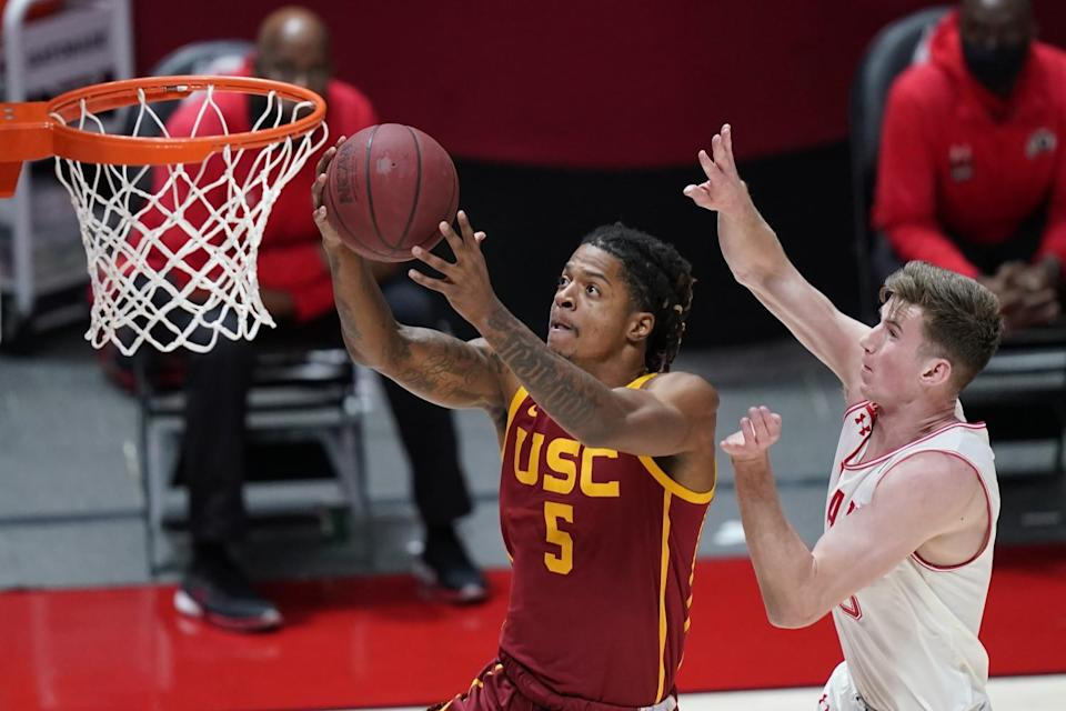 USC guard Isaiah White, left, drives to the basket ahead of Utah center Branden Carlson.