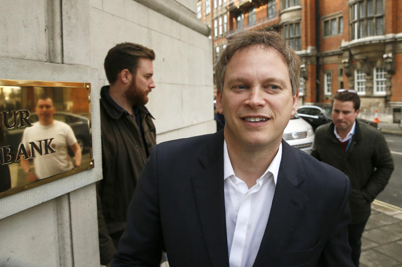 Dean Archer, a chauffeur and former local Labour Party councillor in Welwyn Hatfiled is reflected in a bronze plaque while he speaks to Conservative Party Chairman Grant Shapps as he arrives at television studios in central London, March 25, 2015. REUTERS/Stefan Wermuth