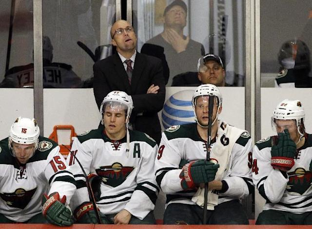 Minnesota Wild head coach Mike Yeo, top, reacts as he looks up a score board during the third period in Game 2 of an NHL hockey second-round playoff series against the Chicago Blackhawks in Chicago, Sunday, May 4, 2014. The Blackhawks won 4-1. (AP Photo/Nam Y. Huh)