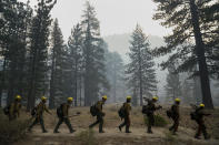 A hotshot crew from Tahoe Hotshots hikes along a trail in Meyers, Calif., Friday, Sept. 3, 2021. Fire crews took advantage of decreasing winds to battle a California wildfire near popular Lake Tahoe and were even able to allow some people back to their homes but dry weather and a weekend warming trend meant the battle was far from over. (AP Photo/Jae C. Hong)