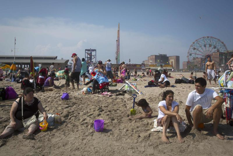 People sit on the beach at Coney Island in the Brooklyn borough of New York