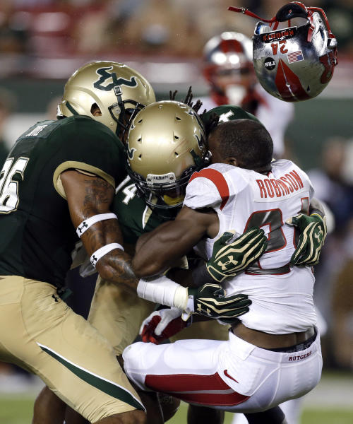 Rutgers' Mason Robinson (24) loses his helmet after a hit by South Florida's Fidel Montgomery (14) and Mark Joyce, left, on a first-quarter attempted punt return during an NCAA college football game Thursday, Sept. 13, 2012, in Tampa, Fla. Robinson fumbled the football and South Florida recovered. (AP Photo/Chris O'Meara)