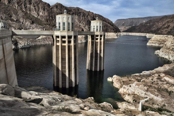 FILE - This March 26, 2019, file photo, shows a bathtub ring of light minerals showing the high water mark of the reservoir which has shrunk to its lowest point on the Colorado River, as seen from the Hoover Dam, Ariz. Six states in the U.S. West that rely on the Colorado River to sustain cities and farms rebuked a plan to build an underground pipeline that would transport billions of gallons of water through the desert to southwest Utah. In a joint letter Tuesday, Sept. 8, 2020, water officials from Arizona, California, Colorado, Nevada, New Mexico and Wyoming urged the U.S. government to halt the approval process for the project, which would bring water 140 miles (225 km) from Lake Powell in northern Arizona to the growing area surrounding St. George, Utah.(AP Photo/Richard Vogel,File)