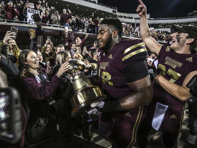 Mississippi State offensive lineman Tyre Phillips (78) celebrates with fans and holds the Golden Egg trophy following the team's 21-20 win over Mississippi in an NCAA college football game Thursday, Nov. 28, 2019, in Starkville, Miss. (Bruce Newman/The Oxford Eagle via AP)