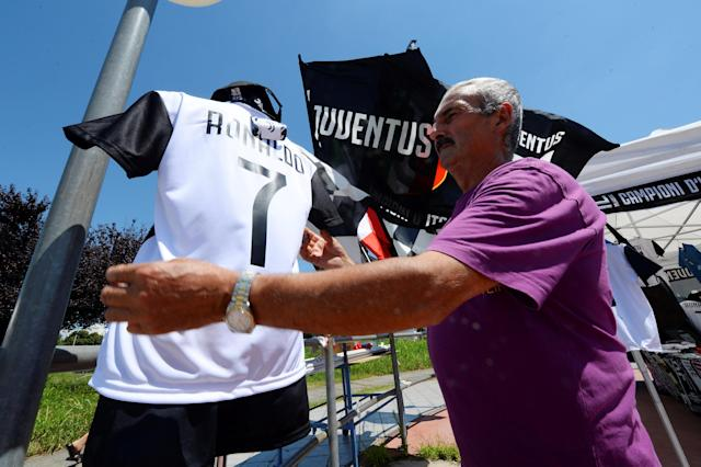A vendor adjusts a Juventus' jersey with the name of Cristiano Ronaldo exhibited in his shop in Turin, Italy July 7, 2018. REUTERS/Massimo Pinca